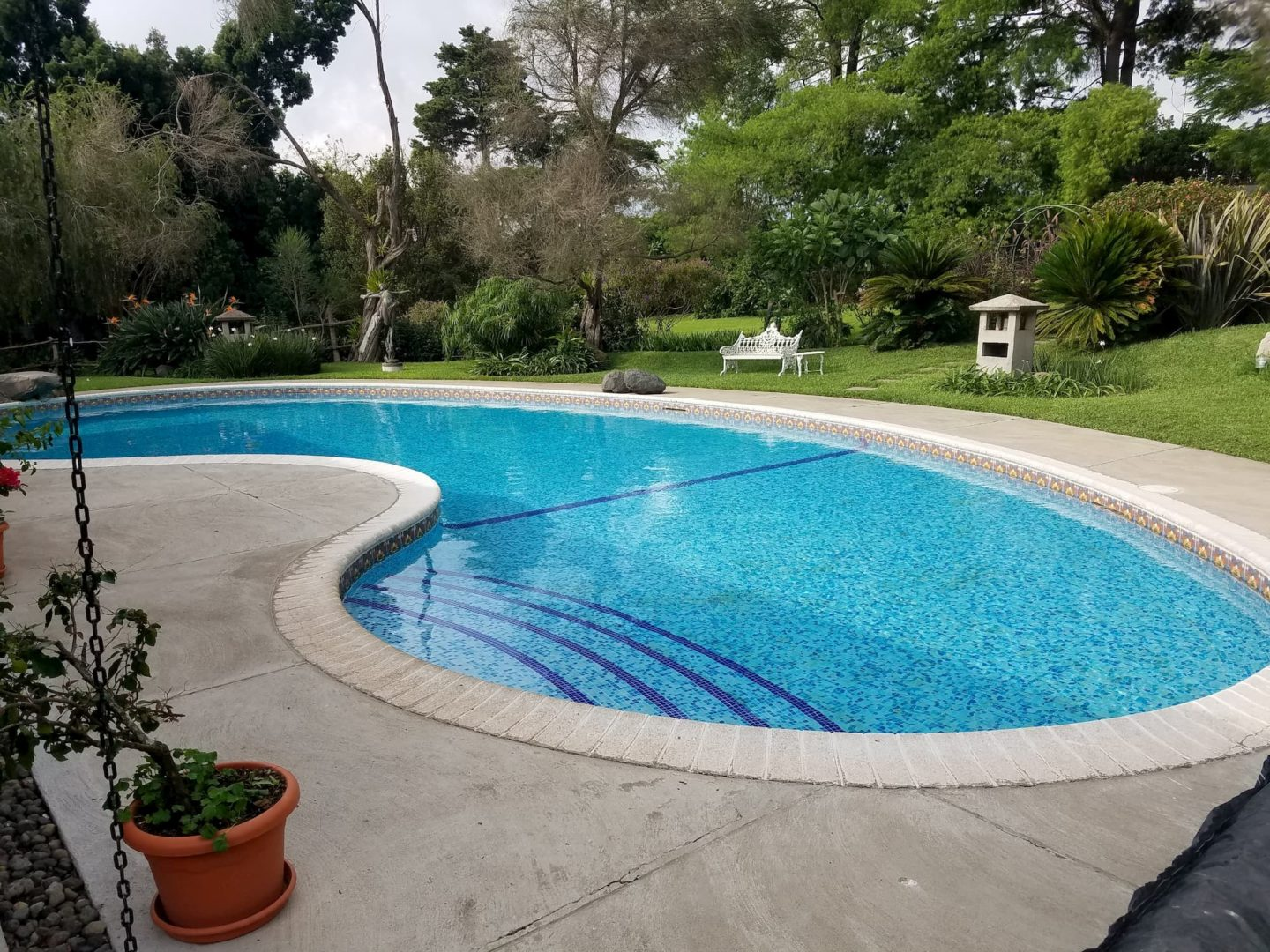Blue pool in the backyard, beautiful yard - Does a Pool Add Value to Your House