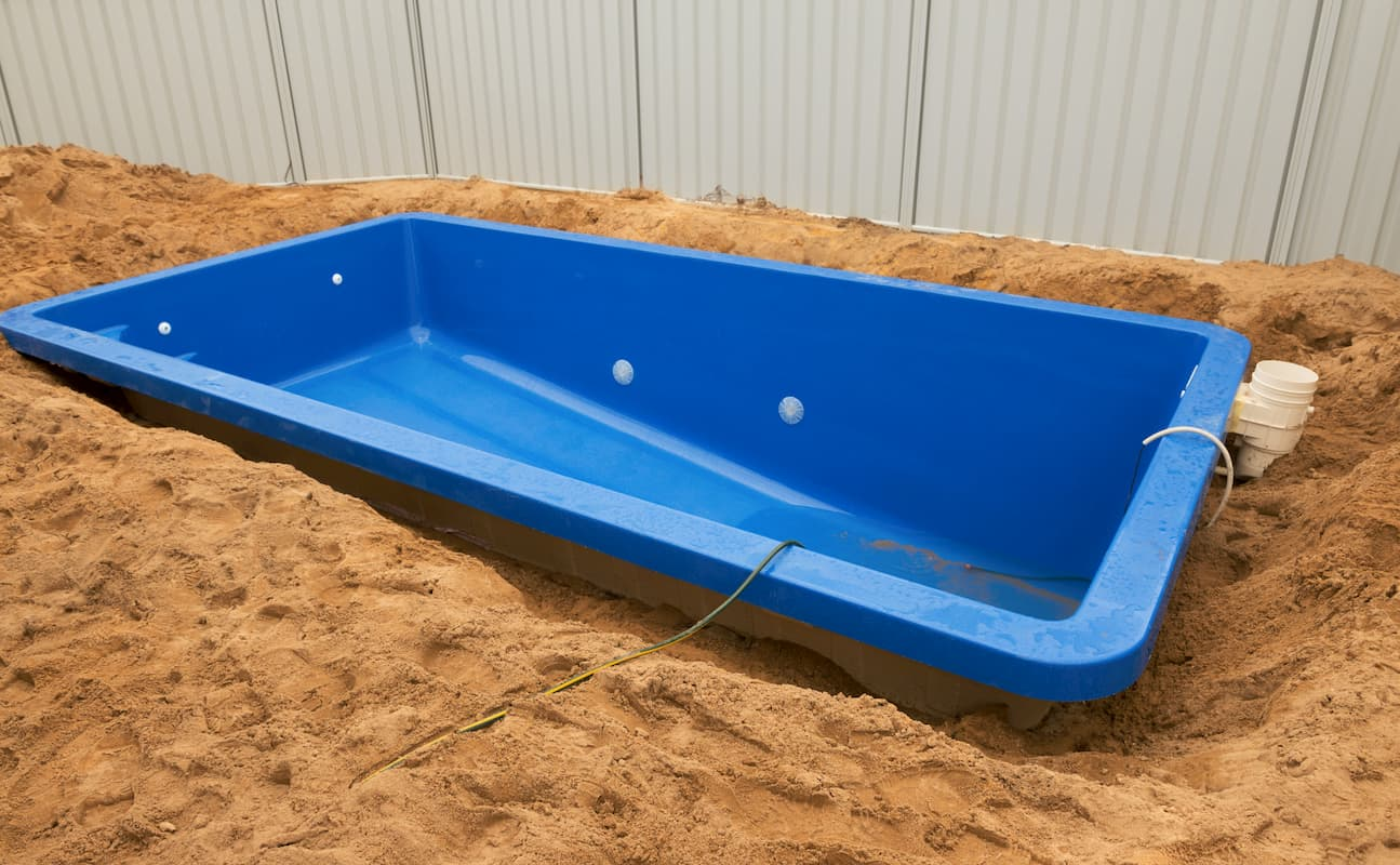 Fiberglass pool tub being lowered into the ground - How Much Does an Average Fiberglass Pool Cost?