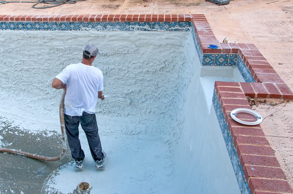 Man standing inside pool with hose spraying pool texture -