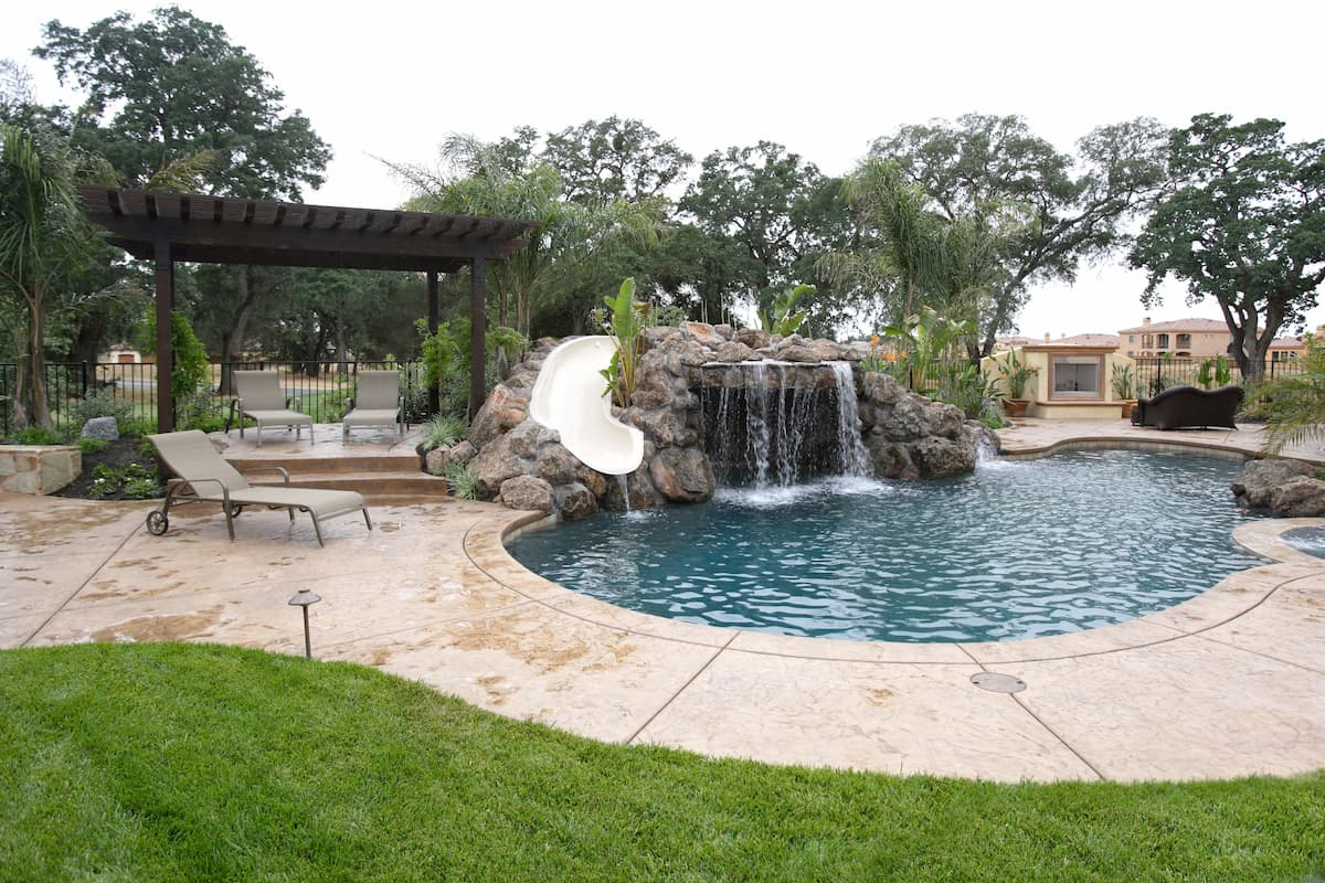 pool with a waterfall in a luxury backyard - How Deep Does a Pool Have to be for a Jumping Rock
