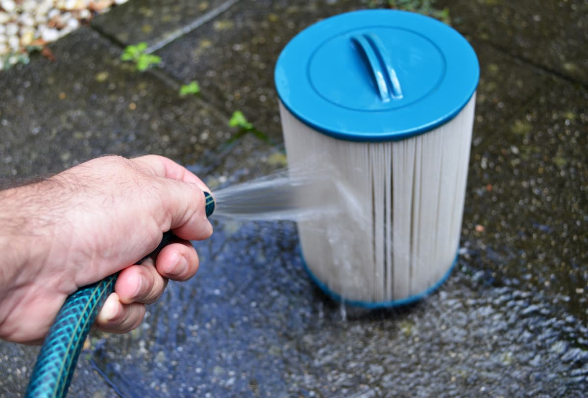 Spraying out the hot tub filter with a hose - How Much Does a Hot Tub Cost to Run