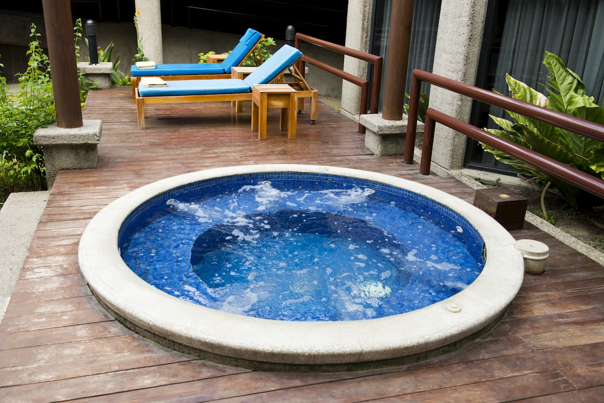 Lawn chairs on a wood deck at a luxury resort hotel sit by a hot tub water spa - How Much Does a Hot Tub Cost to Run