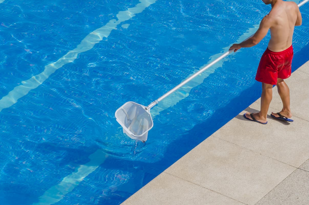 Pool Guy skimming the pool surface - Do You Really Need a Pool Guy?