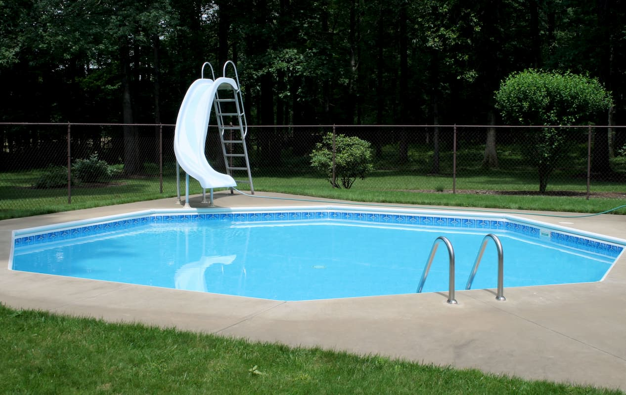 swimming pool and slide enclosed in a fenced-in area - Whats a Safe Pool Depth for a Slide