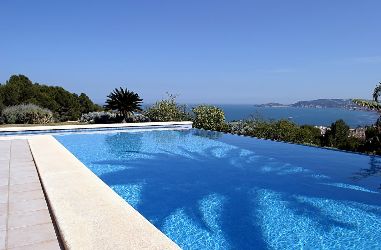 Beautiful blue fresh infinity swimming pool in a villa in sunny Spain with sea views