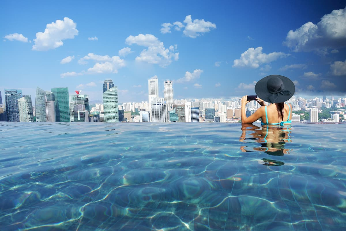 Attractive woman relaxing and enjoying the view in Marina Bay sands infinity pool, Singapore