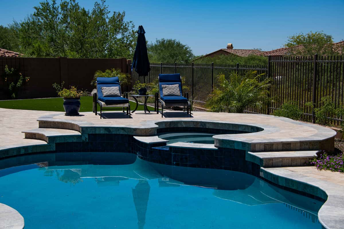 A salt water pebble tech pool and spa with a <a class=